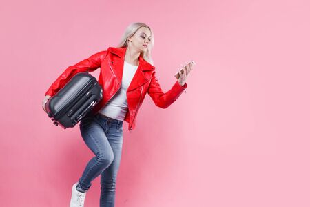 Cheerful young woman tourist hurries to the airport with her Luggage. A girl in a red jacket looks at the smartphone screen, the flight schedule Reklamní fotografie