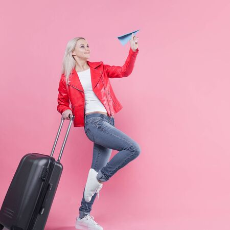 Cheerful young woman tourist hurries to the airport with her Luggage. A girl in a red jacket rolls a suitcase on wheels and launches paper airplane, concept of the traveler and camper