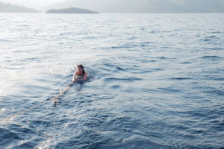pulled out of the water on Board a boat, a young woman swims behind a boat holding on to a rope, having fun or escaping