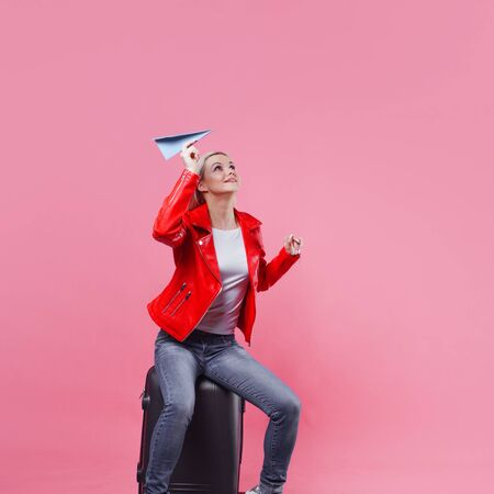 Cheerful young woman tourist hurries to the airport with her Luggage. A girl in a red jacket launches paper airplane, concept of the traveler and camper