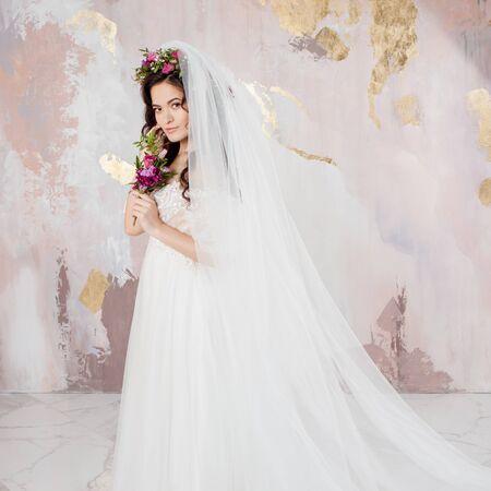 Schöne junge Braut im Hochzeitskleid mit Schleier auf ihrem Gesicht. strukturierter Hintergrund in Pastellfarben