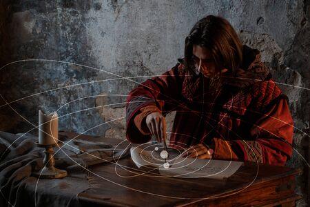 Wissenschaftsgeschichte, das Konzept. Ein junger Mann nach dem Vorbild des Wissenschaftlers des Mittelalters und der Renaissance Nicholas Copernicus, der am heliozentrischen System der Welt arbeitet
