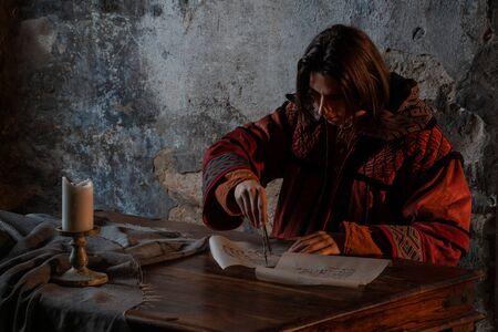 historia del conocimiento científico, el concepto. Un joven a imagen del científico trabaja con manuscritos