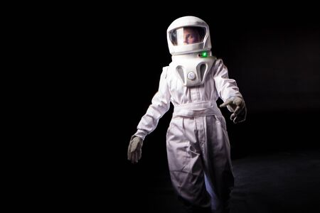 Astronaut on a black background. astronaut in a spacesuit walks forward