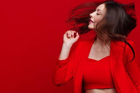 Stylish young woman in a red suit on a red background. One-color image, trendy and bold. Copy space