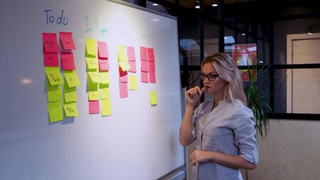 Project management agile methodology, concept. A young blonde woman in glasses, gluing colored sticky notes on a magnetic Board.
