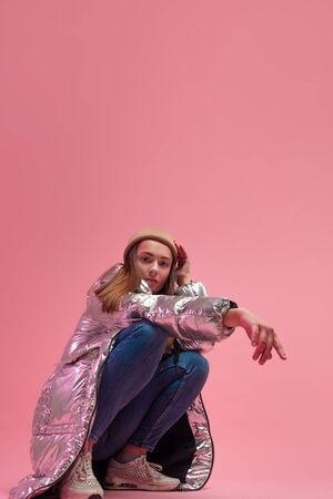 A cool girl in a shiny silver down jacket and a knitted hat squatted down, Studio shot on a pink background, copy space. Stockfoto
