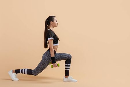 A young brunette girl shakes her gluteal muscles using extra weights, full-length photo, against a peach background. Copy space Banque d'images