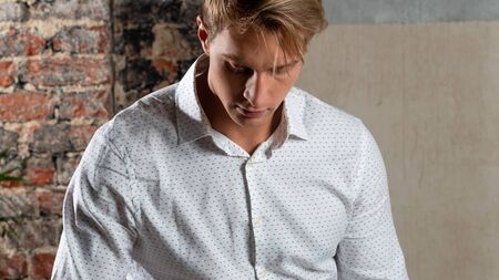 Brooding young man in white shirt, casual style portrait of young businessman Banco de Imagens
