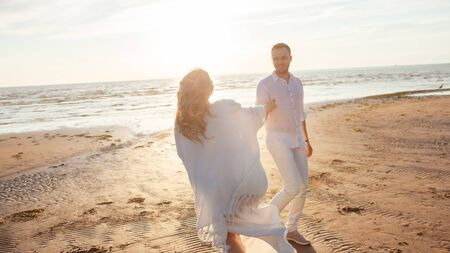 Love, waiting for the baby. A young beautiful couple, pregnant woman and a man, in white loose flying clothes, walk along the sand along the coastline, hold hands, against the backdrop of the sunset. 스톡 콘텐츠