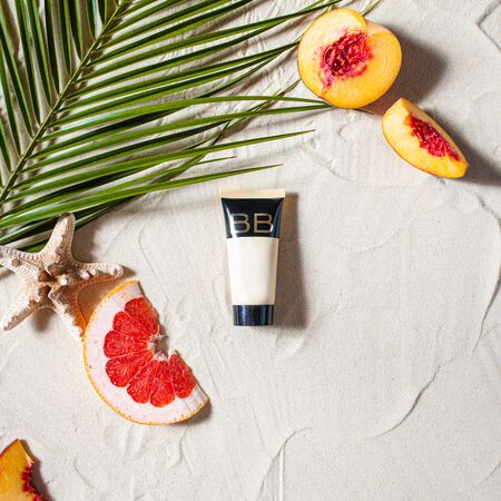 Safe sun. Skin care. A tube of cream lies on the beach sand, surrounded by vibrant fruits, corals, and palm leaves. Close-up, top view, desktop wallpaper. Copyspace. 스톡 콘텐츠