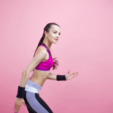 A young brunette attractive girl runs with a smile with wireless headphones and in a bright tight-fitting sports top, on a pink background, cardio. Copy space