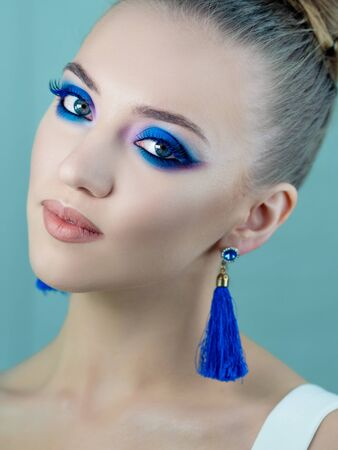 Glamorous bright eye makeup using the trend color classic blue, womens eyes close-up. One tone look with tassel earrings