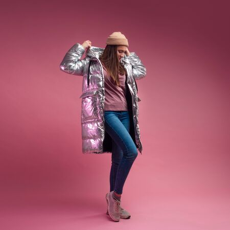 Trendy autumn and winter clothing, Studio shot on a pink background, copy space. A cool girl in a shiny silver down jacket and a knitted hat 스톡 콘텐츠