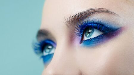 Glamorous bright eye makeup using the trend color classic blue, womens eyes. Close-up of eye makeup, eye shadow in different shades of blue, Blue shadows and earrings 스톡 콘텐츠