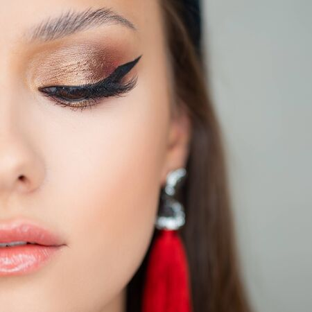 Bright sexy makeup and red tassel earrings. Portrait of a brunette girl, close-up close eye