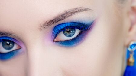 Glamorous bright eye makeup using the trend color classic blue, womens eyes close-up. girl opens her eyes and looks at the camera, Blue shadows and earrings