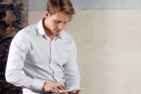 Portrait of a positive and confident young man in a classic white shirt. Happy guy student with the tablet, portrait against gray textured wall