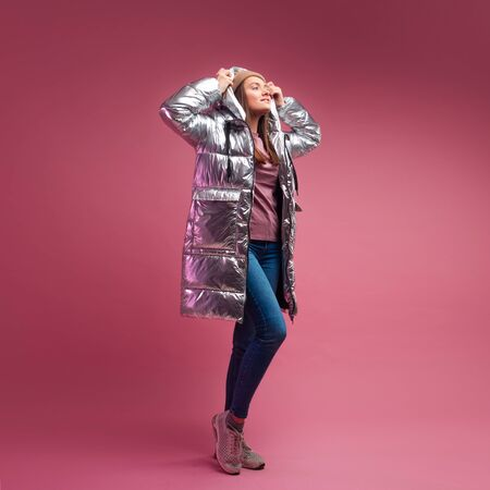 fashionable and modern young woman in a puffy light down jacket throws a hood over her head. The jacket is a silver metallic color. Girl in street clothes, jeans and sneakers, on a pink background