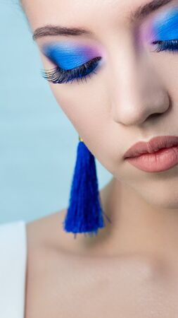 Glamorous bright eye makeup using the trend color classic blue, womens eyes close-up.Close up eyes closed, Blue shadows and earrings