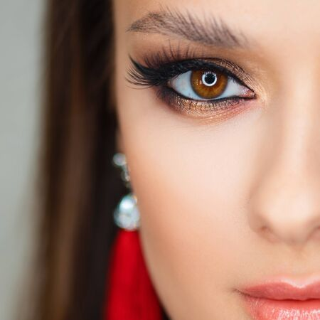 Bright sexy makeup and red tassel earrings. Portrait of a brunette girl, close-up eyes