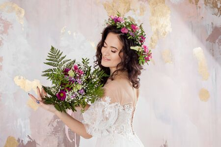 Elegant brunette girl bride with flowers. Beautiful young bride in a lush wedding wreath of fresh flowers. Studio portrait 스톡 콘텐츠
