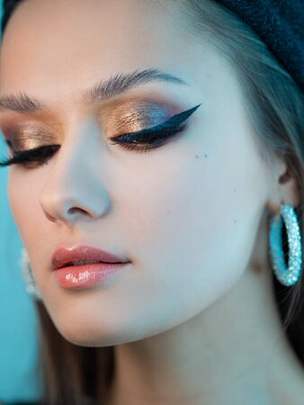 Portrait of a young beautiful brunette woman with bright eye makeup. Image of a southern beauty with earrings rings. Golden eye shadow and eyeliner arrow