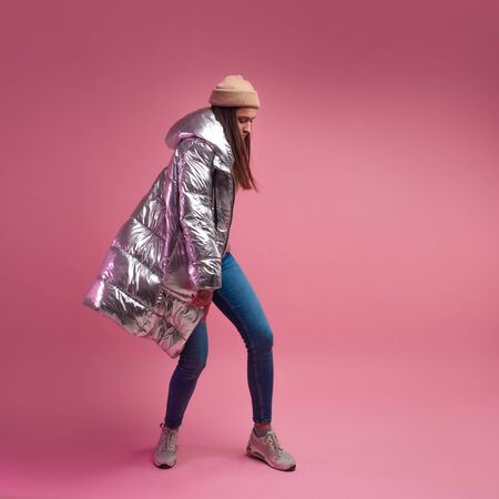 stylish and daring young girl in a silver down jacket dances on a pink background.