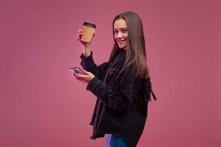 Cheerful and smiling young brunette woman with coffee to go, uses a smartphone, always in touch. Portrait on a pink background