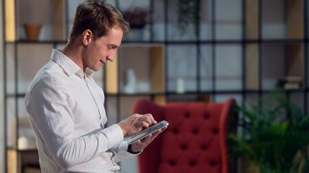 Use of applications and modern technologies for work and communication. Portrait of a positive and confident young man in a classic white shirt. Happy guy student with the tablet 스톡 콘텐츠