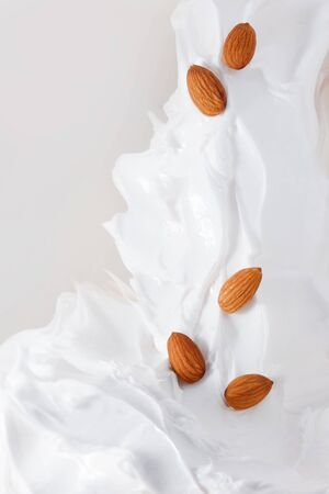 Almond milk. A lot of almonds and milk splash. Cream yogurt and almonds, healthy food 스톡 콘텐츠
