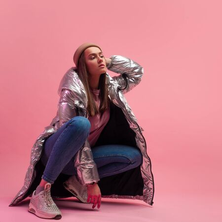Stylish fashionable and modern young woman in a puffy light down jacket. The jacket is a silver metallic color. Girl in street clothes, jeans and sneakers. Sits on a pink background