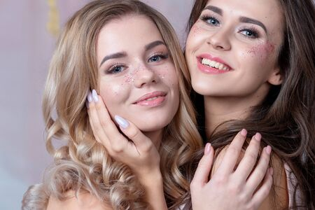 Two happy friends with trendy makeup using glitter on their face. Two young women blonde and brunette, Studio portrait 스톡 콘텐츠