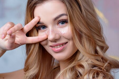 Fun and fashionable girl with sequins on her face. Funny shining blonde shows a two finger gesture