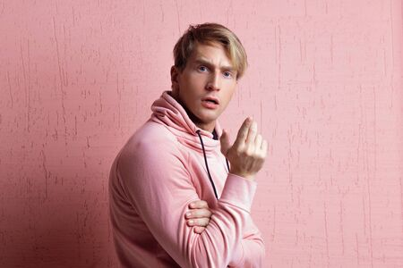 A young man in a pink hoodie on a pink background, portrait of a young stylish guy, emotions of confusion