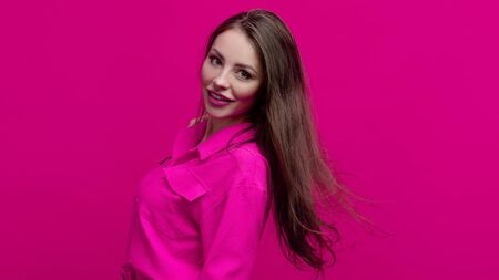 Cute and cheerful young brunette in a pink suit on a pink background. Positive young woman in a bright image, copy space