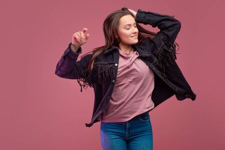 cheerful girl in a fringed jacket dances on a pink background. Happy young brunette, copy space 스톡 콘텐츠