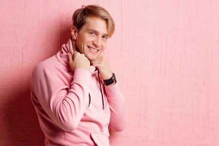 Young man in a pink hoodie on a pink background, happy and smiling. portrait of a young stylish guy