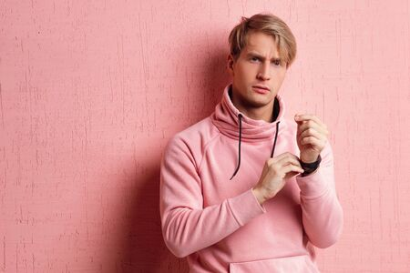 Friendly blond student guy in pink hoodie on pink background, copy space. Portrait of a young man in informal clothes, positive as a lifestyle 스톡 콘텐츠
