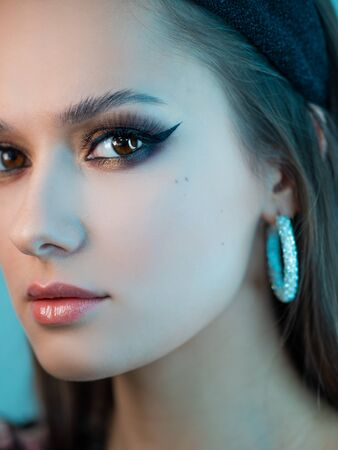 Portrait of a young beautiful brunette woman with bright eye makeup. Image of a southern beauty with earrings rings. Close-up, blue tinting