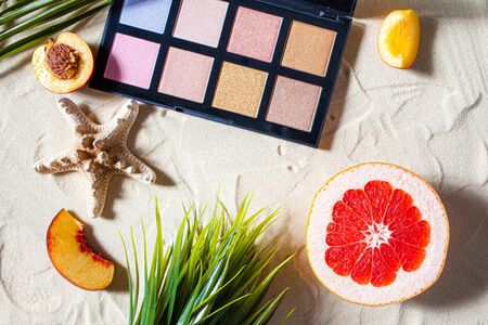 Charming beach. Palette of shadows with square refills surrounded by bright fruits, corals, and palm leaves lie on the white sand. Close-up, top view, desktop wallpaper. Copyspace.