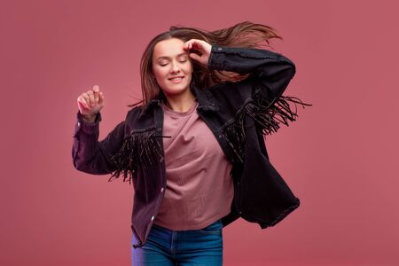 Young brunette woman on pink background. Studio portrait, informal style of clothing, jeans and a cowboy shirt with fringe
