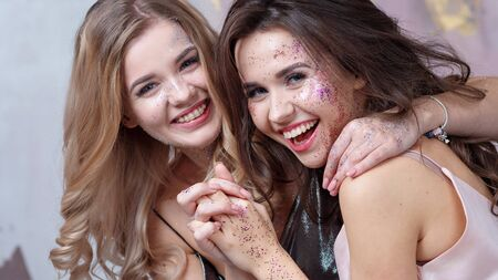 Blonde and brunette with light makeup with added glitter. Shine in an everyday way. Happy smiling girlfriends