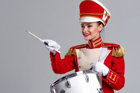 drummer in a red uniform drums on a drum, show program and celebration. Points the sticks to the left