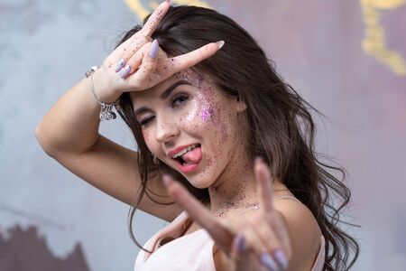 charming brunette with long curly hair, fooling around and showing the tongue. Makeup with sequins on the face