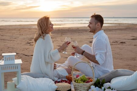 Romantic sunset. A man and a woman had a picnic on the sand, with a blanket, pillows, a lantern, fruit, and sweet pastries. They drink from glasses against the setting sun. Clink glasses.