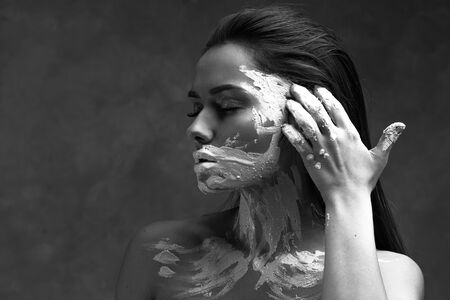 Dumbness and inability to speak about problems and thoughts, psychology. Portrait of a young beautiful woman with paint or clay on her face, shut up and close her mouth. Sad black and white portrait