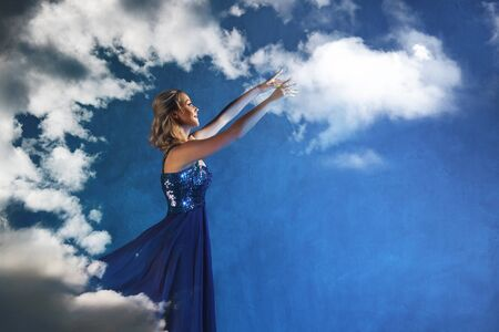 romantic young woman in a blue dress against a blue sky aspires to the clouds. Dreamer girl stretches her hands to the sky