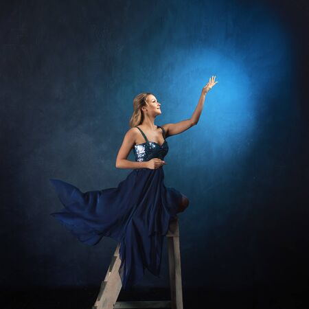 girl on the ladder reaches up with her hands. A young woman in a blue dress on a blue background stretches her hands to the sky, dreamers concept Foto de archivo