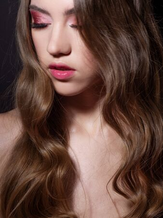 Fashion portrait of a young beautiful woman with long blonde hair. Face with pink makeup, portrait on a dark background